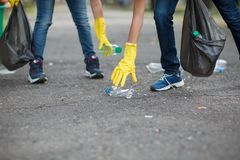 Two children`s hands in yellow latex gloves holding black garbage bags on an asphalt background. Ecology protection. A close-up picture of child`s legs and hands stock image