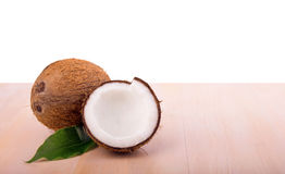 A close-up picture of coconuts on a wooden table. Sweet coconuts isolated on a white background. Exotic and tropical ingredients. A close-up picture of light Stock Photos