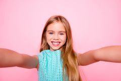 Close up picture of dreamy cute lovely adorable with toothy smil. E little girl with blonde smooth long straight hair, wearing blue dress, taking selfie,  on Stock Photos