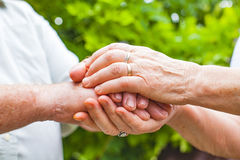 Elderly couple holding hands stock images
