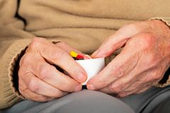Elderly hands holding pills. Close up picture of elderly woman`s hands holding medical pills - illness, influenza, prescription, painkillers stock image