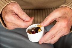 Elderly hands holding pills. Close up picture of elderly woman`s hands holding medical pills - illness, influenza, prescription, painkillers royalty free stock image