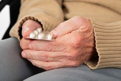 Elderly hands holding pills. Close up picture of elderly woman`s hands holding medical pills - illness, influenza, prescription, painkillers stock photo