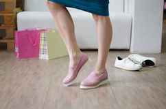 Beautiful woman`s legs wearing seasonal pink boots on a store background. A fashion girl shopping shoes in a shop. royalty free stock image