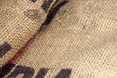 Close up picture of folded crumpled empty old burlap with big printed unrecognisible letters. Ecological, natural fabric packing i stock images
