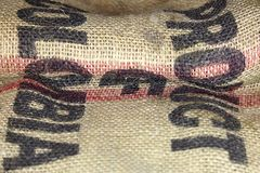 Close up picture of folded empty old burlap with big printed letters. Ecological, natural fabric, background. royalty free stock photo