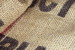 Close up picture of folded empty old burlap with big printed unrecognisible letters. Ecological, natural fabric packing issue, rus royalty free stock image