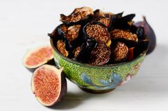 Close-up Picture of Fresh and dried Deep Blue Figs in a green vintage boil covered by green enamel on a white wooden. Fresh and dried Deep Blue Figs in a green stock photos