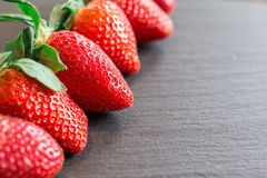 Close up picture of fresh red strawberries lying on a black stone table royalty free stock photos