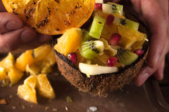 Close up picture of fruit salad in coconut shell. Close up picture of tropical fruit salad in coconut shell. Orange, apple, kiwifruit pieces in nut bowl and stock photo