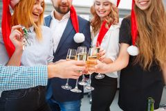 Close-up friends drinking on a Christmas party on a blurred background. New Year celebration concept. Close-up picture of a group of friends cheering and Royalty Free Stock Photography
