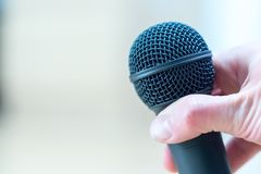 Interview: Journalist is holding a microphone in his hand. Close up stock photo
