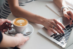 Close up picture of hands of a waiter giving a cup of cuppuccino to a woman typing with a keyboard. Royalty Free Stock Image