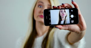 Close-up picture of how female model in her 20s makes photographs of herself on smartphone. stock video