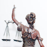 Close up picture of lady justice or themis goddess standing back holding scales blindfold on white background Royalty Free Stock Photos