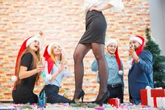Close-up sexy girl dancing on table and friends in Santa hats on a blurred background. New Year fun concept. Close-up picture of long, beautiful woman`s legs Royalty Free Stock Photography