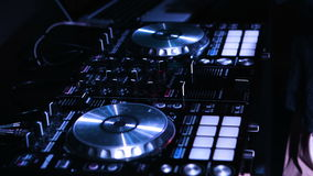 Close-up picture of a male dee-jays hands turning knobs on his music control desk. Panoramic shot. stock video footage