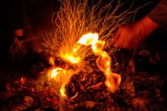 Closeup male hand and bonfire slow shutter picture. Close up picture of man`s hand touching fire with stick taken with slow shutter Royalty Free Stock Photo