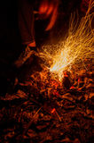 Closeup male hand and bonfire slow shutter picture. Close up picture of man`s hand touching fire with stick taken with slow shutter Stock Images