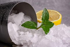 A close-up picture of a metal shaker full of white crushed ice on a gray blurred background. Ice with cut sour lemon and. Close-up of ice shards on a gray stock photo