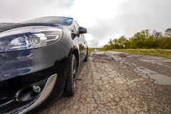 Close-up picture of a modern car on a bad road Stock Images