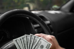 Closeup of american dollars on a wheel. Man`s hand with money on a black car background. Investment concept. Copy space. Stock Photo
