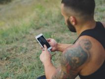 Close-up sports man with a phone. Fit athlete after exercise on a natural background. Technology concept. Copy space. Close-up picture of a muscular, athletic Stock Images
