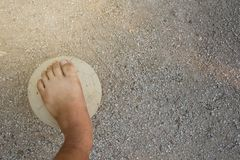 Old ball and foot of a boy who is playing football. Close up picture of an old ball and foot of a boy who is playing football royalty free stock photo