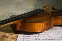 Close-up picture of the old violin witn score Royalty Free Stock Image