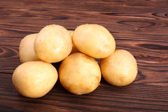 Close-up picture of organic and fresh potatoes on a dark brown wooden background. Raw and delicious young light brown potatoes. Royalty Free Stock Photography