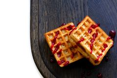 Viennese waffles with jam. Close up picture of a pair of famous viennese waffles with jam served on wide neat dark plate made of dry oak wood. Viennese wafers royalty free stock image