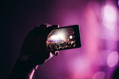 Close-up picture of person holding camera on music festival. Close-up picture of person holding camera and recording video on music festival royalty free stock photography