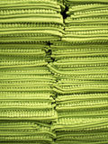 The close up picture of pile ,or stack, of all green rugs. Displayed in two column filled the whole frame. The result creates attractive look of texture Stock Photos