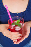 Close up picture of raspberry drink. Close up picture of a young female holding a glass of raspberry juice with ice and mint on  background Royalty Free Stock Image