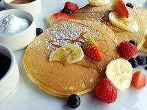 Close-up picture of a sweet breakfast composed of pancakes, fresh berries and fruits, ricotta cheese, jam and honey. stock image