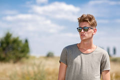A photo of a snazzy young male in sun glasses in a sunny field on a blue sky background. Summer, trip, and rest concept. A close-up picture of a trendy man with Stock Image