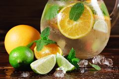 Close-up of a new citrus drink preparation. Green lime, mint and juicy orange with crushed ice on a wooden background. stock photos