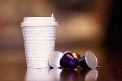 Close up picture of white plastic coffe cup with some colorful replaceable cartridges with coffee. Indoors, copy space, copy atmosphere royalty free stock photos