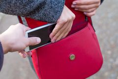 Close up pickpocketing outdoor. Close up picture of woman holding her red bag while a thief trying to steal from her Royalty Free Stock Photography