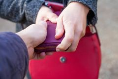 Close up pickpocketing outdoor. Close up picture of woman holding her red bag while a thief trying to steal from her Stock Photography
