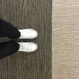 Close-up Picture of Woman Who Crossed Her Legs. Woman in Black Jeans and Sneakers Royalty Free Stock Images