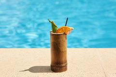 Close up picture of wooden container with cocktail situated near swimming pool on ground. There are black straw, green leaf,. Slices of orange and grapefruit stock images