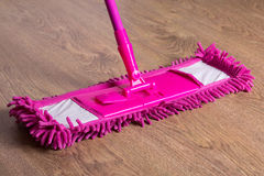 Close up picture of wooden floor with pink mop Royalty Free Stock Photo