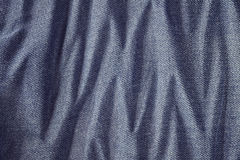 Close up picture of wrinkly blue jeans fabric background. Stock Photos