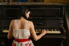 A close up picture of a young woman playing the piano. A close up picture of a young woman playing an old German Uebel Royalty Free Stock Photos
