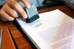 Close-up pictures of the hands of businessmen signing and stamping in approved contract forms stock images