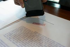 Close-up pictures of the hands of businessmen signing and stamping in approved contract forms royalty free stock photo