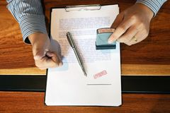 Close-up pictures of the hands of businessmen signing and stamping in approved contract forms stock illustration