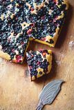 Close-up pie and a piece of berry fruitcake with blueberries and strawberries royalty free stock image