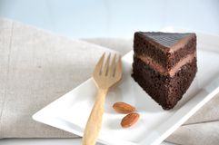 Close up Piece of Chocolate Cake with Almonds. Close up piece of chocolate cake and almonds with wooden fork on white plate stock photo